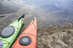 Kayaks stand moored on the shore of the lake. Royalty Free Stock Photography