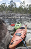 Kayaks stand moored on a stony seashore, in the background of a Stock Photo