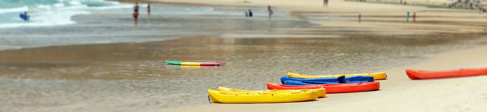 Kayaks and surfboard on a beach Stock Images