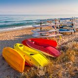 Kayaks and surfboards stored on the sea beach. Stock Images