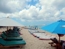 Kayaks, umbrellas and chaise longue Stock Photos