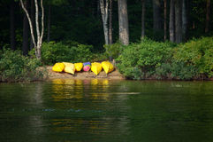 Kayaks waiting. Six colorful kayaks are ready for use on the shores of Thompon Lake Maine stock photo