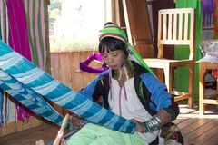 Kayan Lahwi woman. Is weaving cotton and silk thread at the village of Nan Pan, Lake INle, Shan State, Myanmar. The Kayan is a subgroup of Red Karen, Tibeto Royalty Free Stock Photos