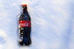 Kazán, Rusia, marzo, 17, 2018: La botella de cristal original de Coca-Cola congelada se pegó en la nieve en puesta del sol brilla Imagenes de archivo