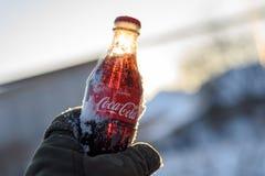 Kazán, Rusia, marzo, 17, 2018: La botella de cristal original de Coca-Cola congelada se pegó en la nieve en puesta del sol brilla Imagen de archivo