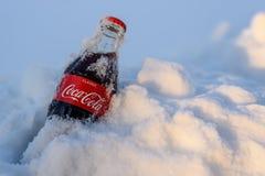Kazán, Rusia, marzo, 17, 2018: La botella de cristal original de Coca-Cola congelada se pegó en la nieve en puesta del sol brilla Imágenes de archivo libres de regalías