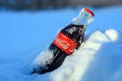 Kazán, Rusia, marzo, 17, 2018: La botella de cristal original de Coca-Cola congelada se pegó en la nieve en puesta del sol brilla Imagen de archivo libre de regalías