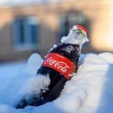 Kazán, Rusia, marzo, 17, 2018: La botella de cristal original de Coca-Cola congelada se pegó en la nieve en puesta del sol brilla Fotografía de archivo