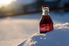 Kazán, Rusia, marzo, 17, 2018: La botella de cristal original de Coca-Cola congelada se pegó en la nieve en puesta del sol brilla Fotos de archivo