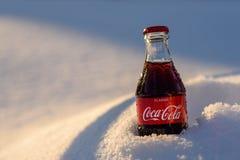 Kazán, Rusia, marzo, 17, 2018: La botella de cristal original de Coca-Cola congelada se pegó en la nieve en puesta del sol brilla Fotos de archivo libres de regalías