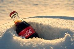 Kazán, Rusia, marzo, 17, 2018: La botella de cristal original de Coca-Cola congelada se pegó en la nieve en puesta del sol brilla Foto de archivo