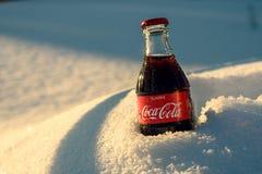 Kazán, Rusia, marzo, 17, 2018: La botella de cristal original de Coca-Cola congelada se pegó en la nieve en puesta del sol brilla Fotografía de archivo libre de regalías