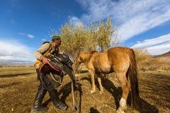 Kazach Berkutchi Eagle myśliwy robi comberu konia Fotografia Royalty Free