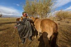 Kazach Berkutchi Eagle myśliwy robi comberu konia W Bayan-Olgii prowincja zaludnia 88,7% Kazakhs Zdjęcia Royalty Free