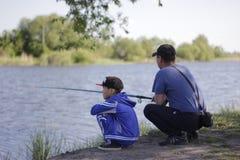 Kazach mężczyzna i jego syn jesteśmy siedzący i łowiący na jeziornym brzeg w lecie Zdjęcie Royalty Free