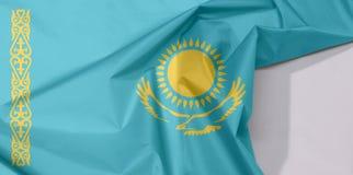 Kazachstan tkaniny flaga zagniecenie z biel przestrzenią i krepa obrazy stock