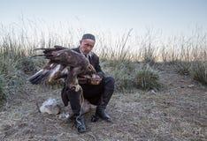 Kazakh adelaarsjager die zijn adelaar voeden Royalty-vrije Stock Foto