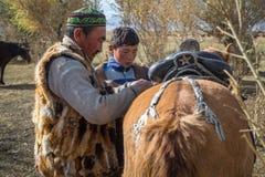 Kazakh Berkutchi Eagle hunters do saddles horse. Royalty Free Stock Images