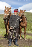 Kazakh boy. Holds the reins of two horses in the pasture Stock Photos