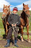 Kazakh boy. Holds the reins of two horses in the pasture Royalty Free Stock Photography