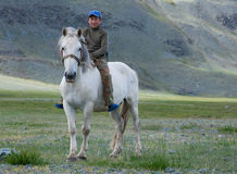 Kazakh boy. Riding a white horse in the mountains of Mongolian Altai Stock Photography