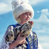 Kazakh bride with a cock. Kazakh bride in festive national dress. Portrait of a rooster in his hands Royalty Free Stock Images