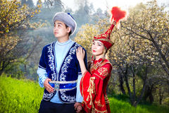 Kazakh couple in ethnic costume. Couple in Kazakh ethnic costume in Spring Blooming apple garden of Almaty, Kazakhstan, Central Asia royalty free stock image