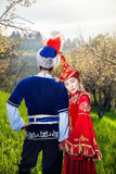 Kazakh couple in love. Couple in Kazakh costume in Spring Blooming apple garden at sunset of Almaty, Kazakhstan, Central Asia Royalty Free Stock Photo