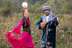 Kazakh couple in national costumes, Almaty, Kazakhstan. Kazakh man plays national musical instrument of dombra  and woman in red dances in Almaty, Kazakhstan Stock Photos