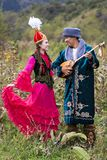 Kazakh couple in national costumes, Almaty, Kazakhstan. Kazakh man plays national musical instrument of dombra  and woman in red dances in Almaty, Kazakhstan Royalty Free Stock Photos
