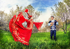 Kazakh couple in traditional costume. Kazakh women dancing in red dress and men playing dombra at Spring Blooming garden in Almaty, Kazakhstan, Central Asia Stock Images