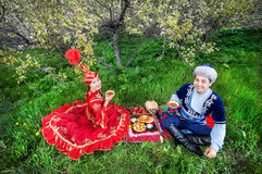 Kazakh culture. Kazakh couple drinking tea on the green grass in apple garden of Almaty, Kazakhstan, Central Asia Stock Photo