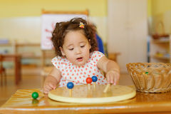 Kazakh curly girl playing in kids development center Royalty Free Stock Images