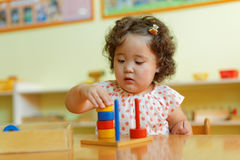 Kazakh curly girl playing in kids development center. Kazakh pretty little girl playing in kids development center Stock Photos