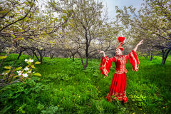 Kazakh dancer in traditional costume. Kazakh woman dancing in red dress at Spring Blooming garden in Almaty, Kazakhstan Royalty Free Stock Photography