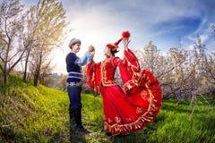 Kazakh dancing. Kazakh women dancing in red dress with men in Spring apple garden in Almaty, Kazakhstan, Central Asia Stock Image