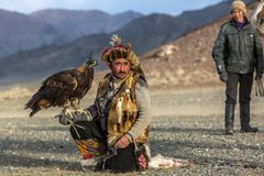 Kazakh Eagle Hunter Berkutchi with horse while hunting to the hare with a golden eagles on his arms. SAGSAY, MONGOLIA - SEP 28, 2017: Kazakh Eagle Hunter Royalty Free Stock Image
