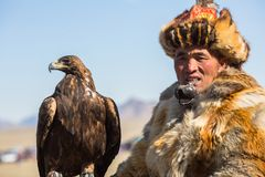 Kazakh Eagle Hunter Berkutchi with horse teaches his daughter to hunting to the hare with a golden eagles. BAYAN-ULGII, MONGOLIA - SEP 30, 2017: Kazakh Eagle Stock Photos