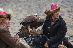 Kazakh Eagle Hunter Berkutchi with horse teaches his daughter to hunting to the hare with a golden eagles. BAYAN-ULGII, MONGOLIA - SEP 30, 2017: Kazakh Eagle Royalty Free Stock Image