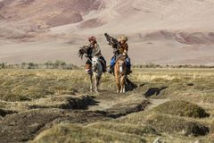 Kazakh Eagle Hunter Berkutchi with horse teaches his daughter to hunting to the hare with a golden eagles. SAGSAY, MONGOLIA - SEP 28, 2017: Kazakh Eagle Hunter Royalty Free Stock Image