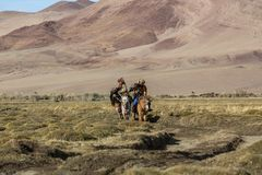Kazakh Eagle Hunter Berkutchi with horse teaches his daughter to hunting to the hare with a golden eagles. SAGSAY, MONGOLIA - SEP 28, 2017: Kazakh Eagle Hunter Royalty Free Stock Photos