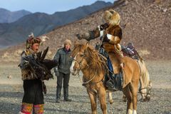 Kazakh Eagle Hunter Berkutchi with horse teaches his daughter to hunting to the hare with a golden eagles. SAGSAY, MONGOLIA - SEP 28, 2017: Kazakh Eagle Hunter Royalty Free Stock Photo