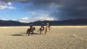 Kazakh Eagle Hunter Berkutchi with horse teaches his daughter to hunting to the hare with a golden eagles
