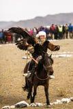 Kazakh Eagle Hunter de Berkutchi en las montañas del aimag de Bayan-Olgii de Mongolia del oeste fotos de archivo