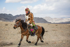 Kazakh eagle hunter on his horse. BAYAN ULGII, MONGOLIA - CIRCA OCTOBER 2015: Kazakh man in traditional clothing on his horse galloping Royalty Free Stock Images