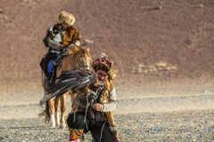 Kazakh Eagle Hunter with horse teaches his daughter to hunting to the hare with a golden eagles in the mountains. SAGSAY, MONGOLIA - SEP 28, 2017: Kazakh Eagle Royalty Free Stock Images