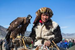 Kazakh Eagle Hunter traditional clothing, with a golden eagle during annual national competition with birds of prey `Berkutchi` royalty free stock photography