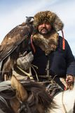 Kazakh Eagle Hunter traditional clothing, while hunting to the hare holding a golden eagle on his arm in desert mountain Stock Image