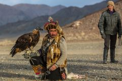 Kazakh Eagle Hunter traditional clothing, while hunting to the hare holding a golden eagle on his arm. SAGSAY, MONGOLIA - SEP 28, 2017: Kazakh Eagle Hunter Stock Photo