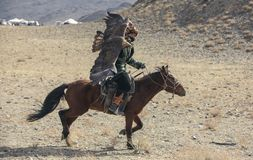 Kazakh eagle hunter traveling on his hotse in a landscape of altai Mountains stock image